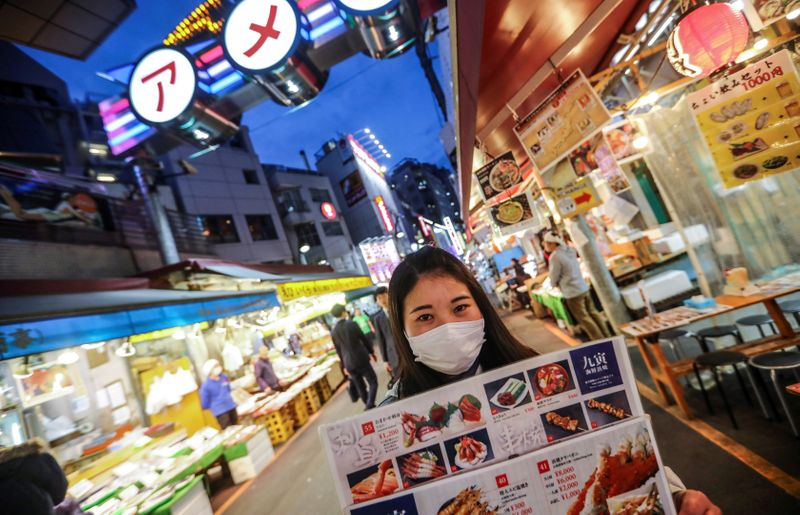 FILE PHOTO: A woman wooing visitors for her restaurant wears a protective face mask in Tokyo