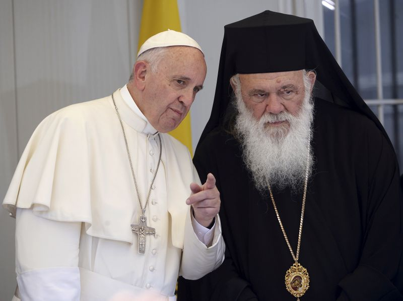 FILE PHOTO: Pope Francis gestures next to Archbishop Ieronymos II on the Greek Island of Lesbos