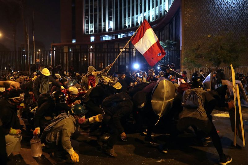 Demonstrators clash with police during protests that led to the resignation of Peru's interim President Manuel Merino, in Lima