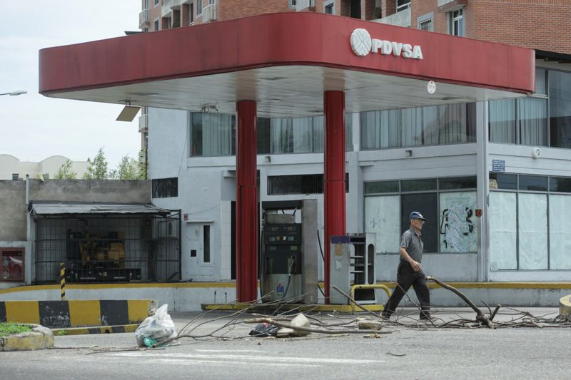 FILE PHOTO: A man walks past a closed gas station of the state oil company PDVSA in San Cristobal