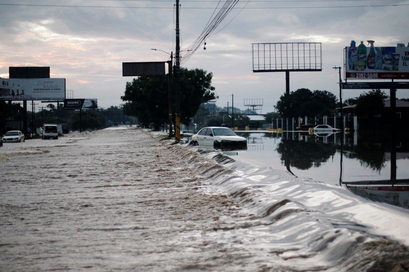 A stranded car is seen at a road flooded by the Chamelecon River due to heavy rain caused by Storm Iota, in La Lima