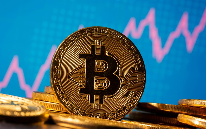 A representation of virtual currency Bitcoin is seen in front of a stock graph