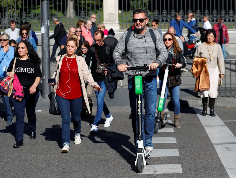 FILE PHOTO: People ride dock-free electric scooters Lime-S by California-based bicycle and scooter sharing service Lime, through a crosswalk in Madrid