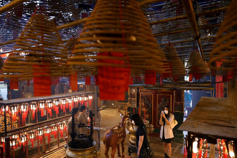 FILE PHOTO: Visitors wearing face masks visit Man Mo Temple for a Hong Kong Tourism Board's free local tour, following the coronavirus disease (COVID-19) outbreak, in Hong Kong
