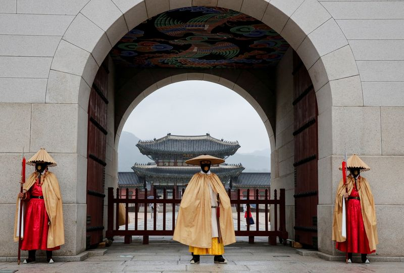 Workers wearing traditional attire wear masks to prevent the spread of the coronavirus disease (COVID-19) during the daily re-enactment of the changing of the Royal Guards at Gyeongbok Palace in central Seoul