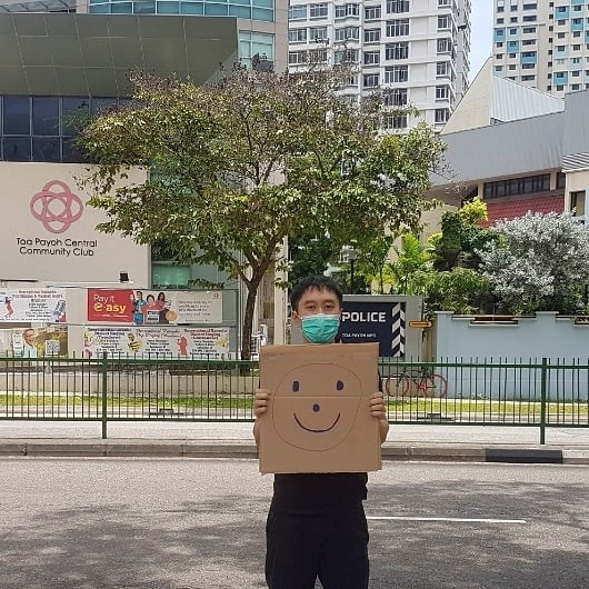 Jolovan Wham wears a mask and holds a cardboard with a drawing of a smiley face in Singapore