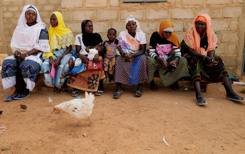 Women who fled from attacks of armed militants in Sahel region of Soum sit at a courtyard of the house in an informal camp for displaced people on the outskirts of Ouagadougou,