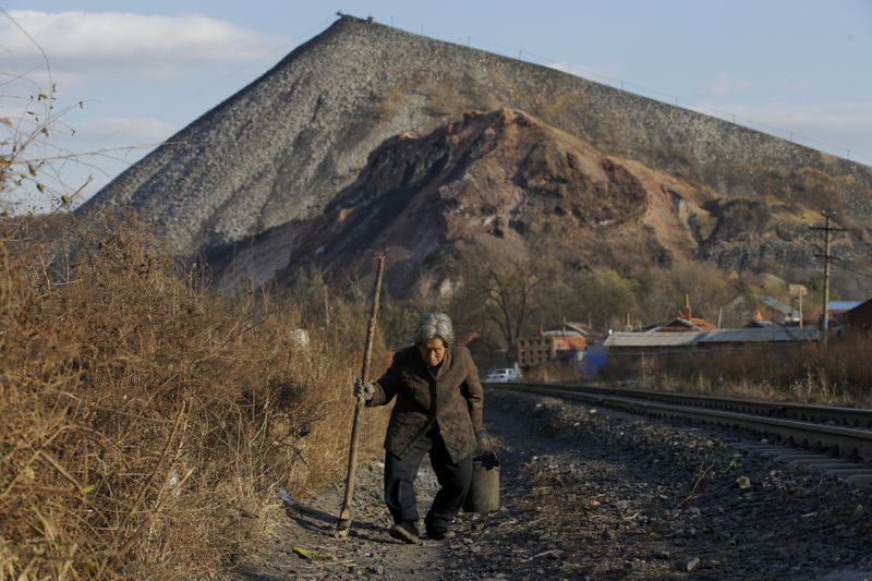 FILE PHOTO: An elderly villager walks along a railway which is used to transfer coal outside Shuanghe coal mine on the outskirts of Jixi in China