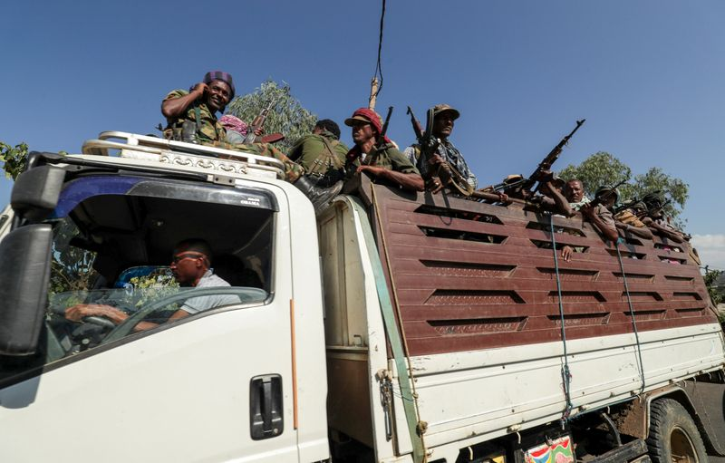 FILE PHOTO: Members of Amhara region militias ride on their truck as they head to face the Tigray People's Liberation Front in Sanja