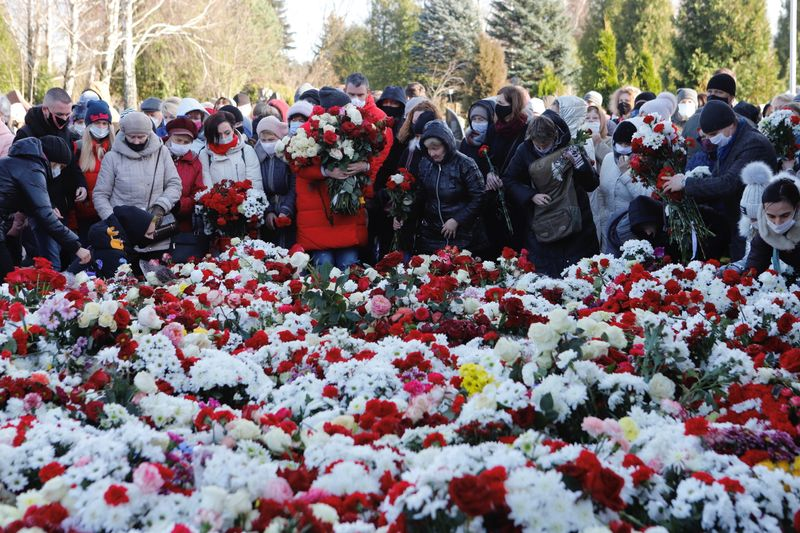 People lay flowers during a funeral of anti-government protester Roman Bondarenko in Minsk