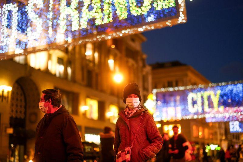 Pedestrians illuminated by Christmas lights walk through Oxford Street amid the coronavirus disease (COVID-19) outbreak in London