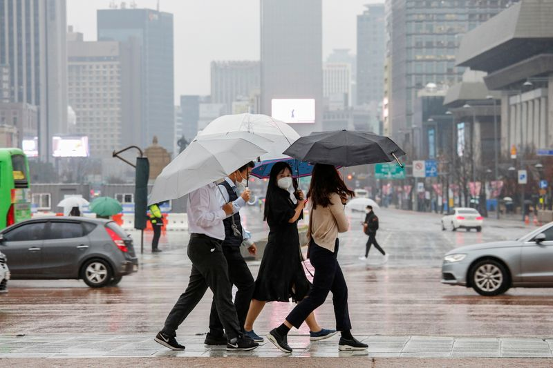Pedestrians wearing masks walk with umbrellas as it rains amid the coronavirus disease (COVID-19) pandemic in central Seoul