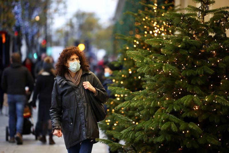 A woman walks past Christmas trees on Oxford Street, amid the coronavirus disease (COVID-19) outbreak, in London