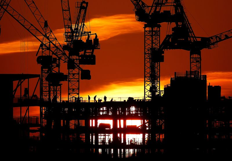 Workers are seen as the sun sets behind a construction site in London