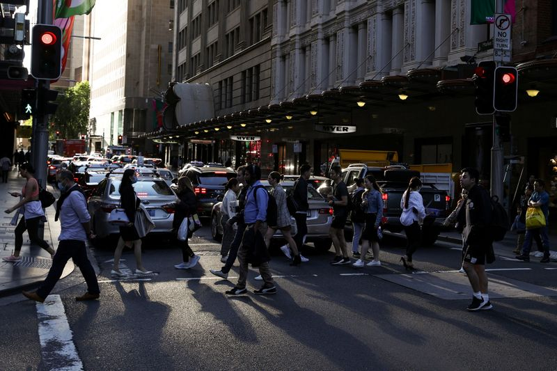 People walk through a congested intersection in the city centre of Sydney