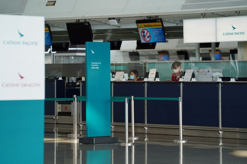 Cathay Pacific employees are seen behind counters with glass dividers at Hong Kong International Airport